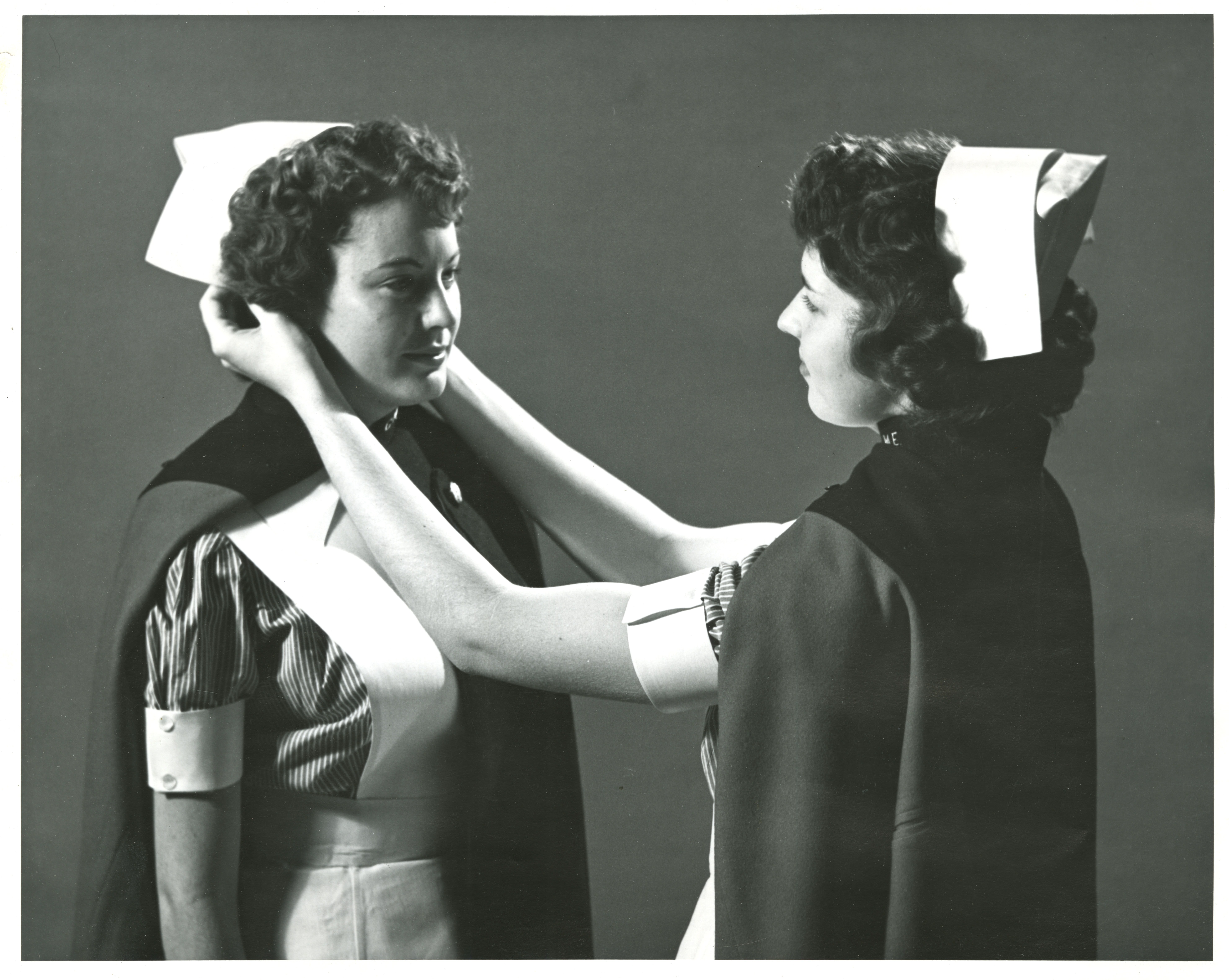 A photograph of student nurses in uniforms performing the capping ceremony, which is part of the graduation ceremonies.